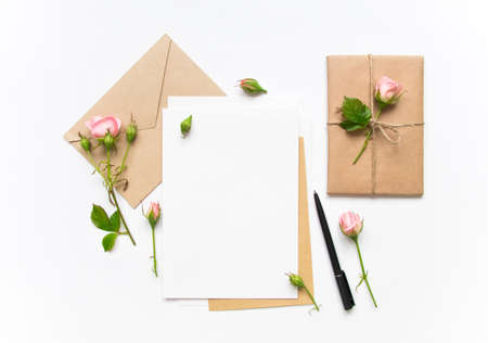 Letter, envelope and a present in eco paper on white background. Wedding invitation cards or love letter with pink roses. Valentine's day or other holiday concept, top view, flat lay, overhead view