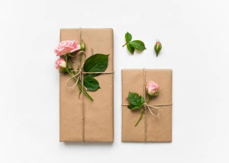 Vintage gift boxes in eco paper on white background. Presents decorated with rose flowers and leaves. Valentines day or other holiday concept, top view, flat lay, overhead view