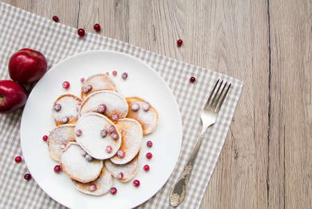 checker plate: Home made pancakes with cranberries and sugar powder on a white plate. Wooden table, rustic decoration, berries, apples and a fork. Top view, flat lay, view from above