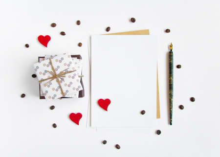 white day: Handmade gifts and a letter on white background decorated with hearts and coffee beans. Rustic style, cute paper DIY decoration. Valentines day or other holiday concept. Flat lay, top view Stock Photo