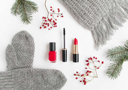 Winter accessories collage with cosmetics, woolen scarf and mittens decorated with berries and fir tree on white background. Flat lay, top view