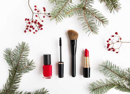 冬化粧品コラージュは、モミの木の枝と白い背景の上の果実で飾られて。ブラシ、爪のポーランド語、マスカラー口紅組成物を構成します。フラッ