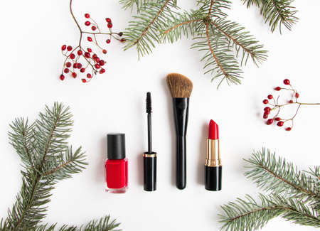Winter cosmetics collage decorated with fir tree branches and berries on white background. Lipstick, mascara, nail polish and brush, make up composition. Flat lay, top view Stock Photo