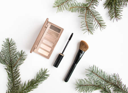 flat brush: Winter cosmetics collage decorated with fir tree branches on white background. Eye shadows, mascara and brush, make up composition. Flat lay, top view