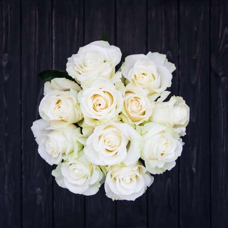 Perfekter Strauß cremefarbener Luxus-Rosen für Hochzeit, Geburtstag oder Valentinstag. Schwarzer alter hölzerner Hintergrund, Draufsicht, flache Lage