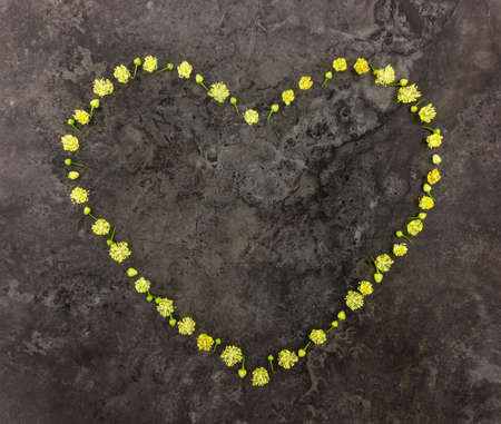 heart symbol: Heart symbol made of small linden flowers on dark marble stone background. Valentines day composition. Flat lay, top view