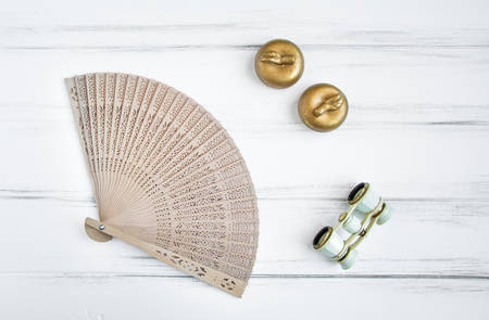 vintage objects: Overhead flat lay shot of feminine objects a woman uses in preparation for a visit at the opera or theater: lorgnette and wooden fan, candles. Vintage flat lay, top view Stock Photo