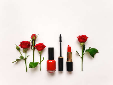 applicator: Decorative flat lay composition with woman cosmetics and red rose flowers. Flat lay, top view on white background, make up composition