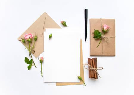 Letter, Umschlag und ein Geschenk in Öko-Papier auf weißen Hintergrund. Hochzeitseinladungskarten oder Liebesbrief mit rosa Rosen. Valentinstag oder anderes Urlaubskonzept, Ansicht von oben, flach liegt, Draufsicht