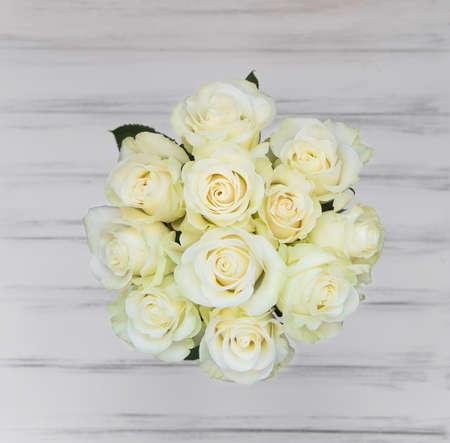 rosas blancas: ramo perfecto de rosas de lujo crema para la boda, cumpleaños o el día de San Valentín. Blanco viejo fondo de madera, vista desde arriba, en posición plana