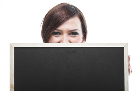 obscuring: Smiling woman with a blank chalkboard or blackboard with a clean slate partly obscuring her face so that just her eyes are visible, isolated on white with copyspace for your text Stock Photo