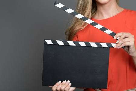 producing: Close up a blond woman with her face not shown holding a movie clapperboard.