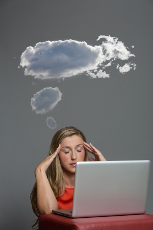 in somnolence: Blond woman sitting in front of her laptop with her eyes shut with dark clouds above her.