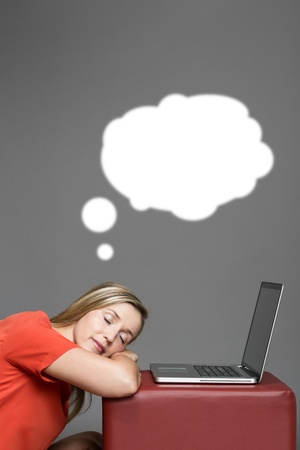 in somnolence: Office worker dreaming sweet dreams as she sleeps on the job resting her head on her arms in front of her laptop computer, upper body portrait on grey with a white thought bubble for your text