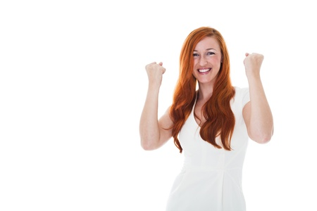 jubilation: Excited young redhead woman celebrating a victory punching the air with her fists in jubilation, upper body isolated on white