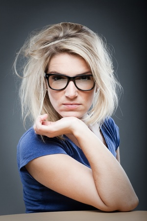 bad hair day: Woman wearing glasses having a bad day and glaring at the camera with her blond hair in a tousled mess Stock Photo