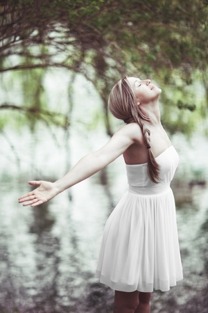 outspread: Beautiful young woman in a fresh white summer dress standing with her arms outspread rejoicing in the joys of nature