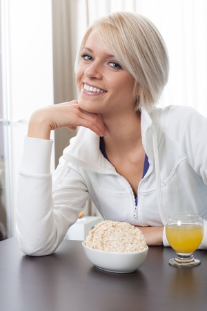 Beautiful stylish young woman with a friendly smile seated at a table enjoying a healthy breakfast photo