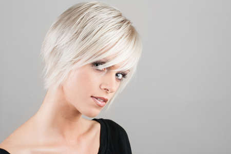 Beautiful young woman with a trendy blonde hairstyle, head and shoulders portrait on a grey studio background photo