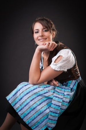 Beautiful young Bavarian woman in traditional dress sitting with her chin resting on her hand smiling at the camera photo