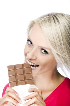 tempting: Attractive blond woman biting into a tempting bar of chocolate with a look of joyful anticipation, isolated on white