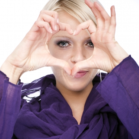 Beautiful young blond woman making a romantic heart sign with her fingers in front of her face isolated on white photo