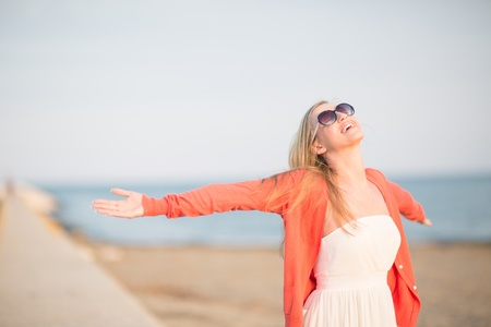 outspread: Beautiful woman rejoicing at the sea standing with her arms outspread embracing the sun Stock Photo