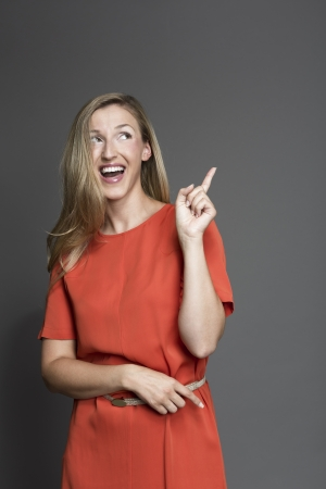 endorsing: Happy woman posing and looking up while pointing at something Stock Photo