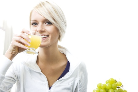 Beautiful friendly woman with a lovely smile drinking fresh orange juice from a glass photo