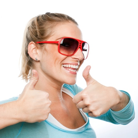 high spirited: Vivacious enthusiastic blond woman wearing sunglasses giving a thumbs up of approval with a beaming smile, isolated studio portrait