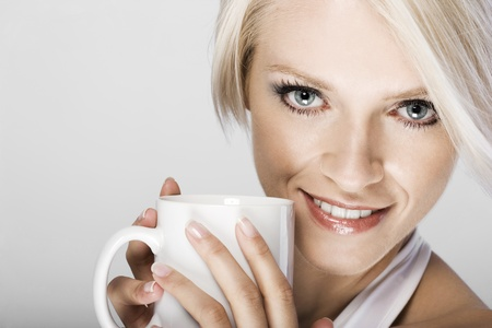 Beautiful young woman with a mug of coffee and large soulful eyes looking at he camera, cropped closeup studio portrait photo