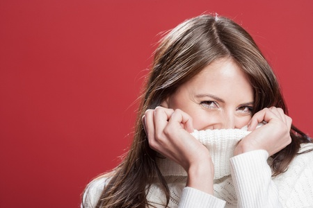 amused: Shy young woman hiding inside the neck of her polo neck pullover while smiling at the camera, head and shoulders studio portrait on red Stock Photo
