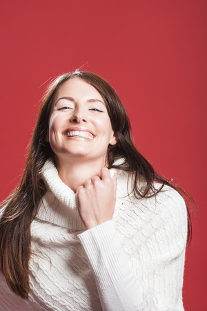 vivacious: Laughing vivacious woman with a beaming smile in a polo neck pullover, studio portrait over red