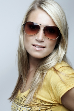 Beauty portrait of a beautiful young blond woman wearing sunglasses looking to the camera with a seductive expression photo
