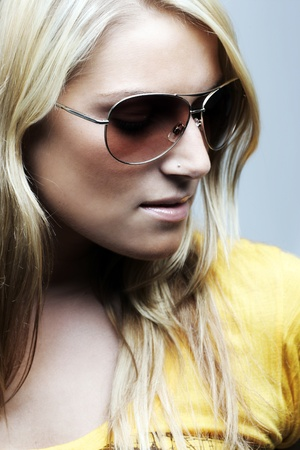 Close-up portrait of a beautiful blond woman wearing sunglasses and with a serious expression photo