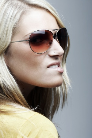 Closeup portrait of a beautiful blond woman with sunglasses looking over her shoulder and biting her lower lip photo
