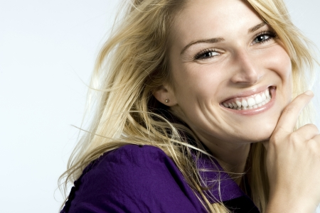 Portrait of a joyful beautiful blond woman with blue eyes showing an open smile and looking at the camera photo