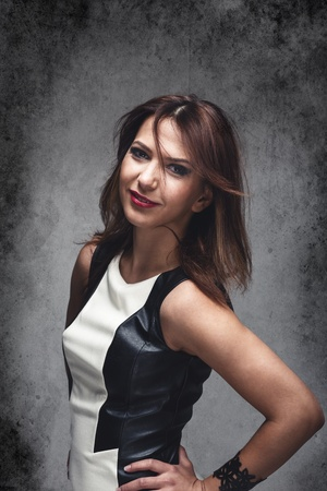 close fitting: Cool trendy modern woman wearing a stylish close fitting black and white dress standing with her hands on her hips looking at the camera, upper body studio portrait on grey