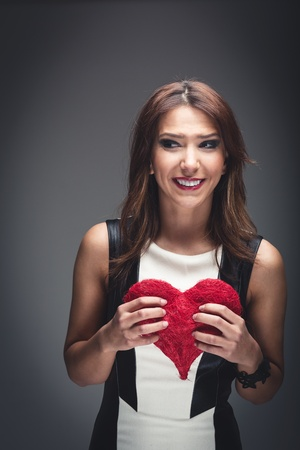 Beautiful woman in a trendy black and white dress holding a red Valentines heart in her hands in front of her chest, studio portrait on grey photo