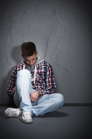 Young man feeling depressed sitting on the ground leaning against a wall and looking down wearing blue jeans and a checkered sweater photo