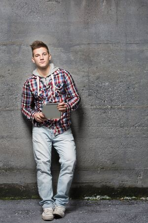 Portrait of a young man looking at camera, using a tablet, standing and leaning against a wall outside photo