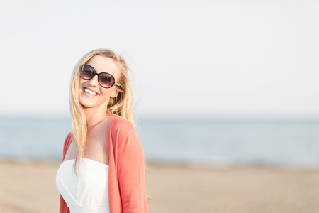 Laughing woman wearing sunglasses at the seaside on a beautiful summer day with copyspace photo