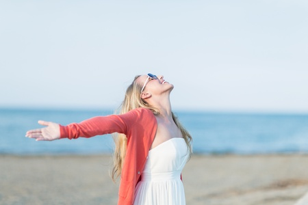 �xtasis: Mujer regocijo en la posici�n del sol de verano en la playa con los brazos extendidos y la cabeza inclinada hacia atr�s a la luz del sol con una sonrisa de �xtasis