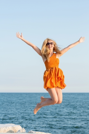 outspread: Attractive young woman wearing sunglasses and a colourful orange summer dress jumping for joy at the sea with her arms outspread