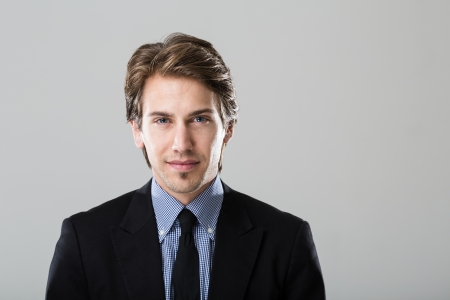 Portrait of a young businessman on grey background looking directly at camera photo