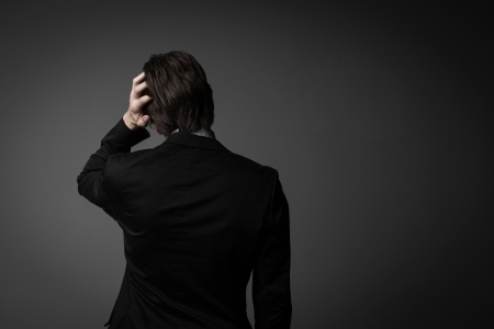 bad times: Studio shot of a male model expressing bad times by facing the wall and one hand on his head, isolated on gray. Stock Photo