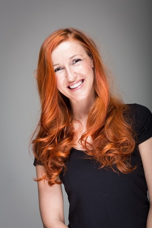 Friendly warmhearted woman with a lovely smile and gorgeous wavy red hair, studio portrait on grey photo