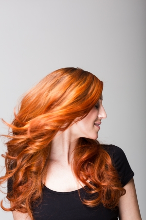 Profile of a cool redhead woman tossing her gorgeous long wavy hair so that it is flying loose around her face photo