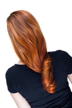 Woman with beautiful long red hair with a fiery copper colour standing with her back to the camera photo