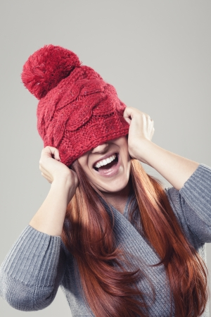 mirth: Playful and smiling pretty woman wearing a red winter beanie with bobble stuck to her nose covering the eyes